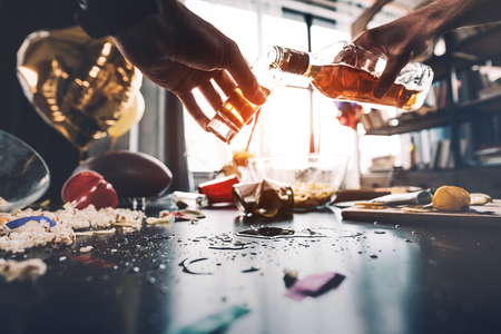 man pouring whiskey into glass after party