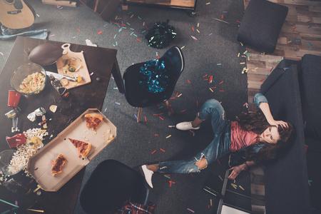 mujer borracha joven tendido en el suelo en la habitación desordenada
