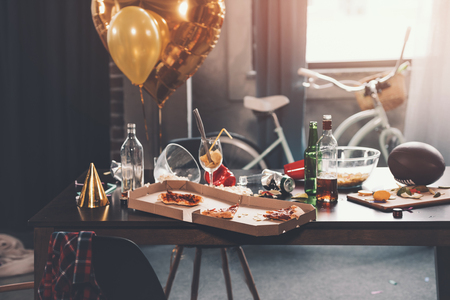 Messy table with pizza in box and beverages at morning