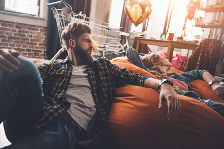 man and woman resting on beanbag chair in messy room after party