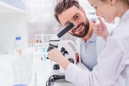 수염이 많은 교사가 실험실에서 현미경으로 일하는 작은 학생을보고 스톡 콘텐츠