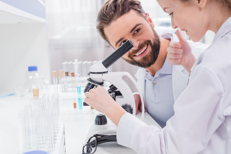 bearded teacher looking at little student working with microscope in lab