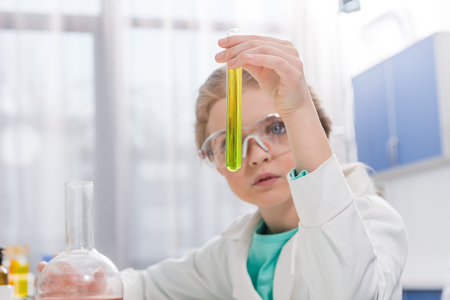 little girl in goggles with reagents in flasks in laboratory Фото со стока