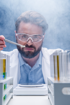 chemist in goggles with reagents in tubes and tablet in laboratory Stock Photo