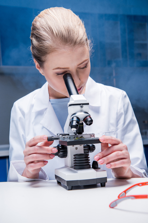 attractive blonde scientist working with microscope in laboratory