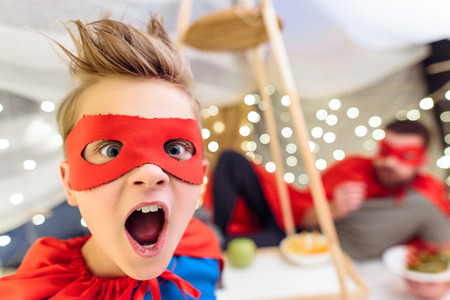 excited little boy in superhero costume looking at camera