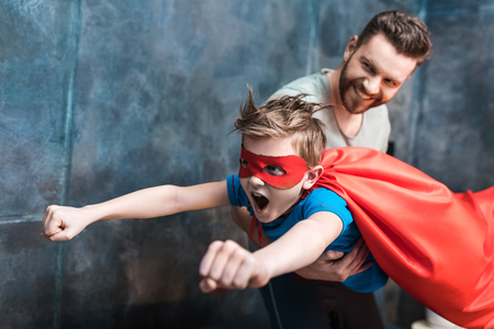 father holding son in superhero costume flying