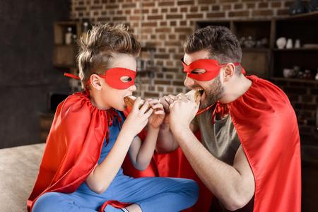 père et fils en costumes de super-héros rouges, manger des sandwichs