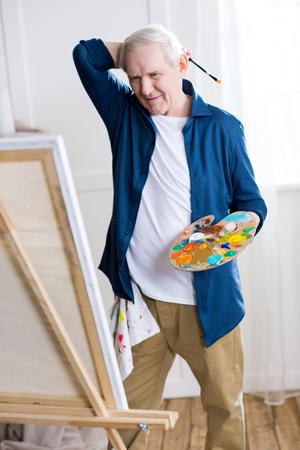 senior man drawing picture in art workshop