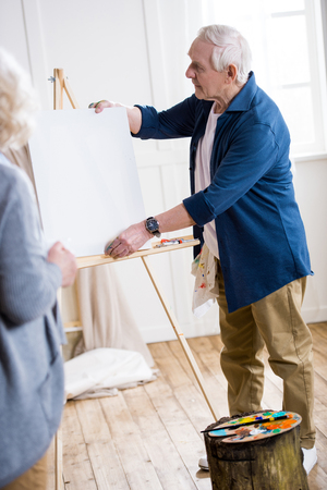 easel: man getting ready to draw woman portrait in workshop