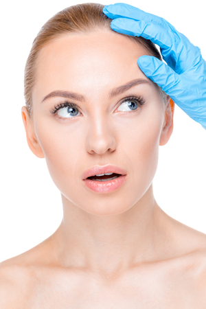 cosmetologist examining face of patient