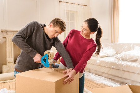 smiling woman helping man packing things for moving home Stock Photo
