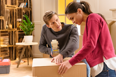 young couple packing things for moving home