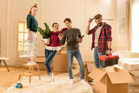 move in: friends holding different things for moving into new house Stock Photo