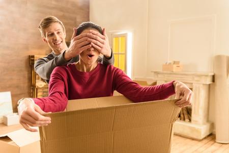 남자 새 집에서 손으로 여성의 눈을 감고