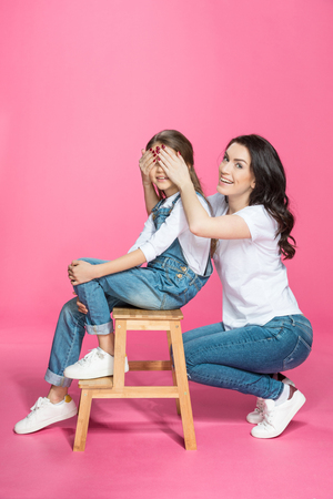 stool: mother covering eyes to cute smiling daughter sitting on stool