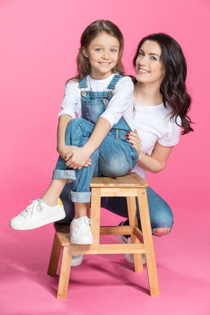 stool: happy mother and cute little daughter smiling at camera