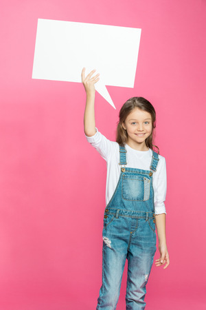 smiling little girl holding blank speech bubble on pink Stock Photo