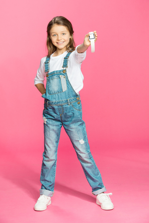 little girl in denim overalls holding smartwatch and smiling Stock Photo