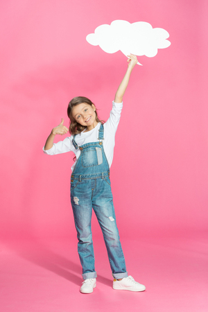 dungarees: smiling little girl holding blank speech bubble and showing thumb up
