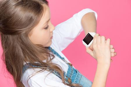 schattig klein meisje met behulp van smartwatch op roze Stockfoto