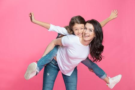 Moeder piggybacking schattige kleine dochter lachend op camera