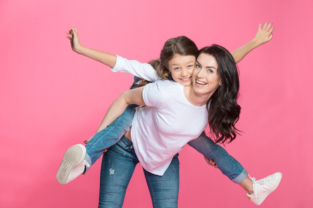 mother piggybacking adorable little daughter smiling at camera