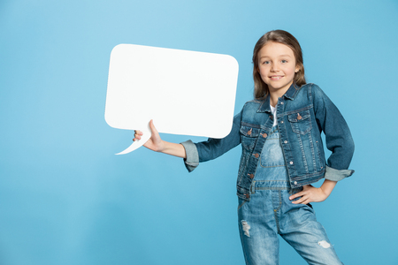little girl with hand on hip holding speech bubble on blue