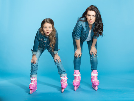 tired mother and daughter in roller skates in studio