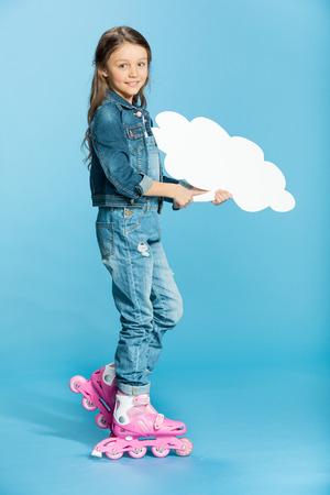 little girl in pink roller skates holding speech bubble in studio