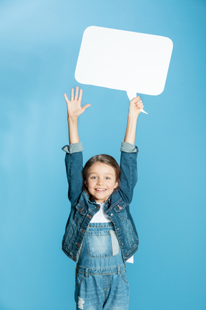little girl with raised hands holding speech bubble and looking at camera Stock Photo