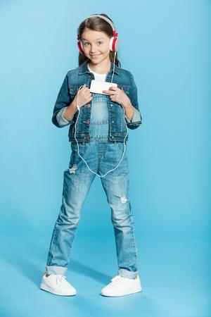 petite fille dans les écouteurs à l'aide de smartphone en studio sur bleu