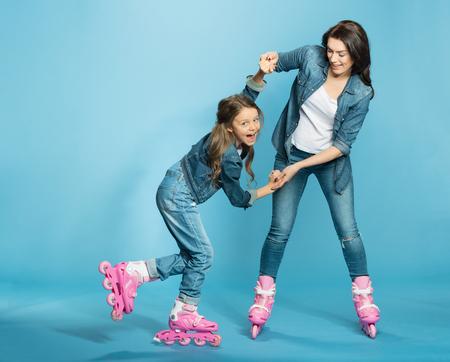 mother and daughter in roller skates having fun in studio