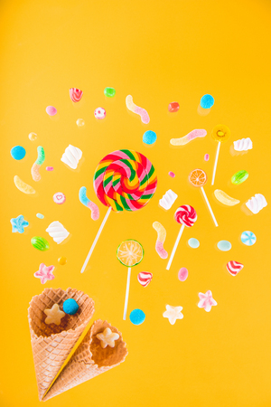 Close-up top view of waffle cones and mix of various sweets on yellow background