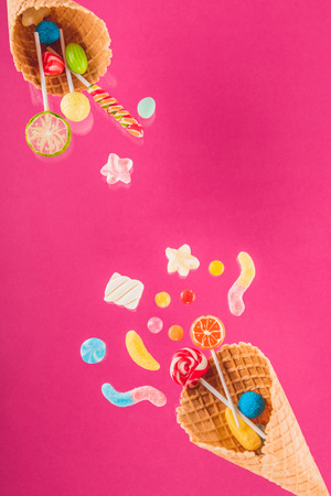 waffle cones with different delicious jelly candies and lollipops on pink Stock Photo
