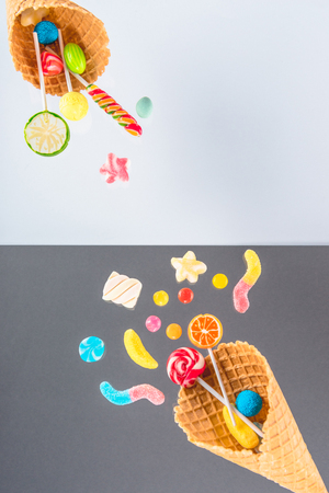 waffle cones with different delicious jelly candies and lollipops on white and grey