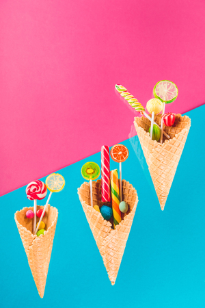 waffle cones with different delicious jelly candies and lollipops on blue and pink