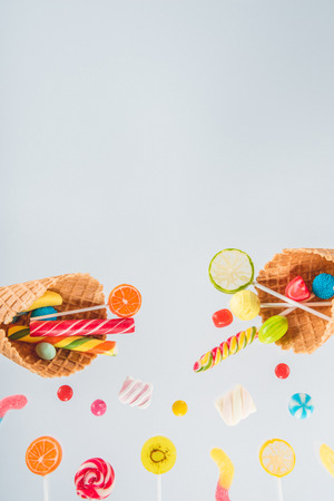 waffle cones with different delicious jelly candies and lollipops on white Stock Photo