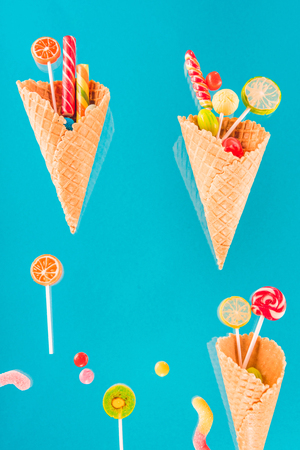 waffle cones with different delicious jelly candies and lollipops on blue