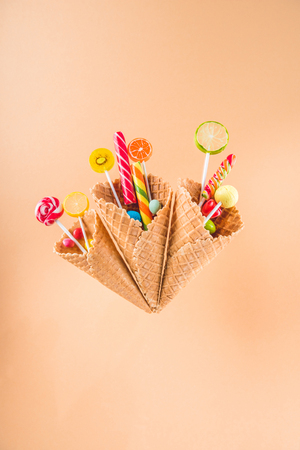 waffle cones with different delicious jelly candies and lollipops on beige Stock Photo