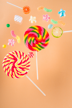 different colorful delicious jelly candies and lollipops on beige