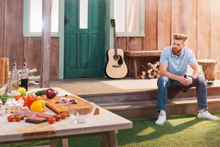 bebaarde jonge man zit op de veranda en het drinken van bier