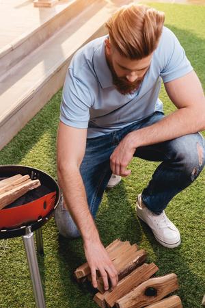 bebaarde jonge man brandhout voor outdoor grill kijken
