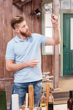 bearded young man holding empty glass while standing at table outdoors Banco de Imagens