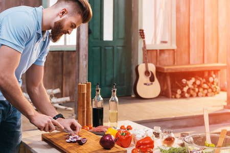 bearded young man cutting onion for barbecue Banco de Imagens