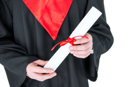 Close-up partial view of young man in graduation gown holding diploma