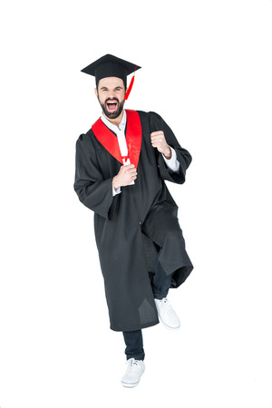 triumphing: Excited young man in graduation hat holding diploma and triumphing