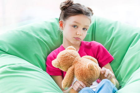 Petite fille sérieuse assise dans une chaise sac de haricots et tenant un ours en peluche Banque d'images