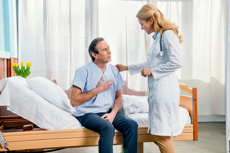 middle aged man with chest pain and doctor standing near him Stock Photo