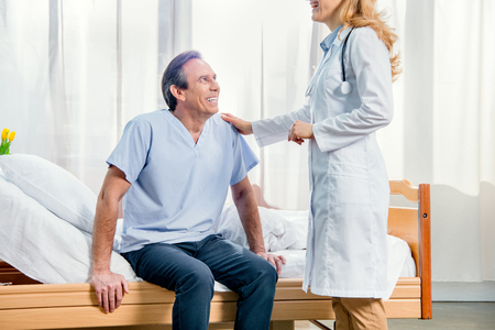 middle aged patient sitting on bed and doctor standing near him